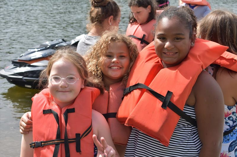 Summer camp lake fun with kayaks, canoes and paddle boats where boys and girls lose weight and have fun