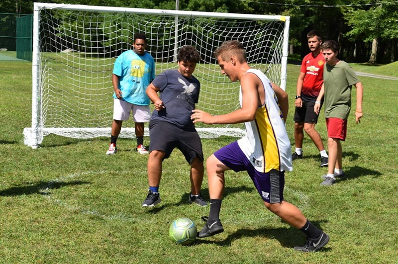 Boys playing soccer on the courts by their comfortable cabins at world famous summer fitness camp