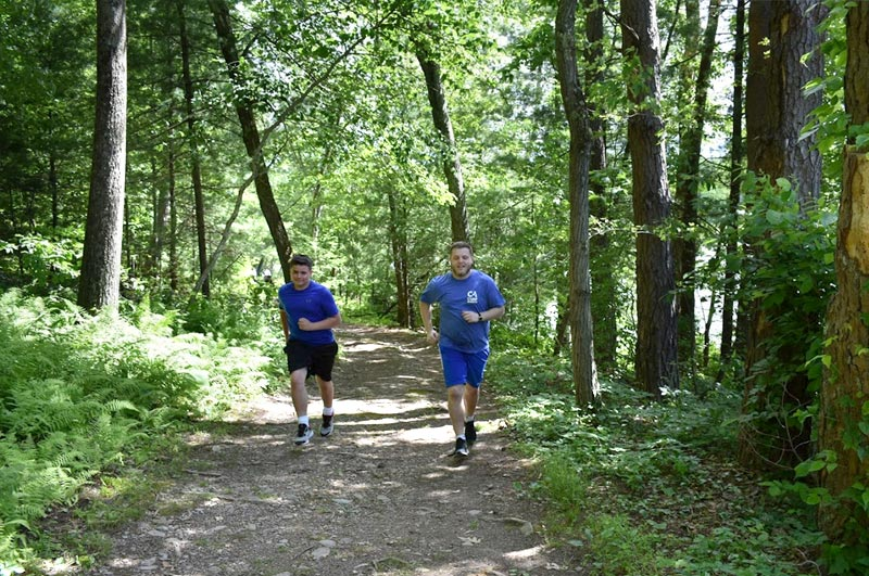 Boys jogging through the woods and getting fit at our lakefront summer weight loss camp by Tony Sparber