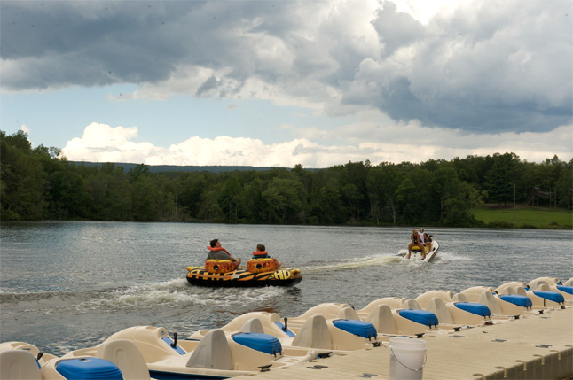 Kids & teens enjoy water sports with tubes & a jetski at lakefront summer wellness camp in Reeders, PA by Tony Sparber